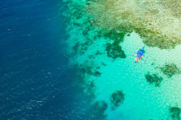Boat on a coral reef. Sea surface with an atoll, coral reefs. Sea shoal and depth. Seascape with tourist boat.