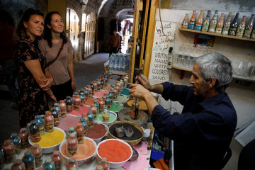 Tourists look on as Palestinian craftsman Mohammed Al-Awawda creates coloured sand artworks at his souvenir shop in Hebron, in the Israeli-occupied West Bank