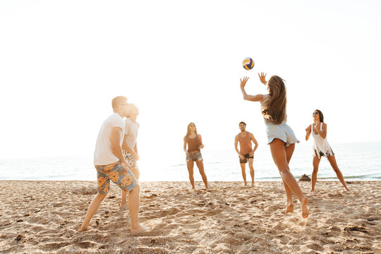 Group of cheerful friends playing volleyball