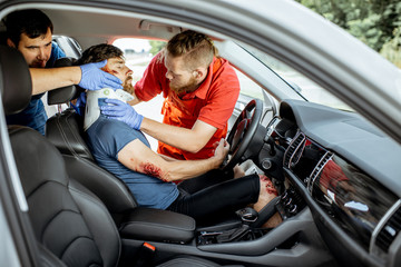 Medics wearing neck corset to an injured man sitting in the car after the road accident, providing emergency medical assistance
