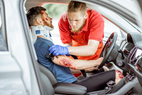 Medic wearing tourniquet on arm of injured person sitting on the driver saet after the road accident, providing emergency medical assistance