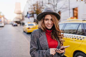 Good-looking businesslady in gray hat gently smiling, walking down the road. Stunning dark-haired female model in coat standing beside taxi in morning.