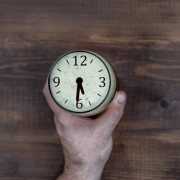 Close up man's hand holds a mug of beer with a silhouette of a clock showing half past six. Concept of alcohol abuse and problems with potency. Top view