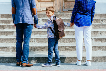 Unrecognizable parents take child to school. Pupil of primary school go study with backpack. Rear view of father, mother, son stands hand in hand. Child look back at camera.