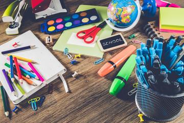 Colorful school supplies over wooden desktop. Back to school