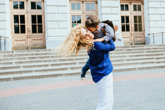 Meeting after school. Happy mother and son running, hugging, whirling to meet each other in front of the school building outdoor.