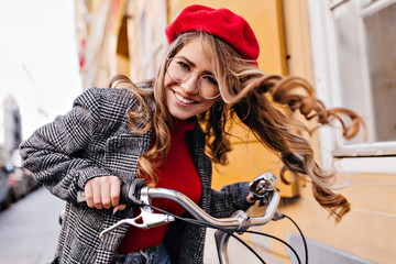 Outdoor portrait of emotional curly lady exploring town on bike. Sensual french girl in red beret having fun, riding on bicycle in autumn day. Fototapete