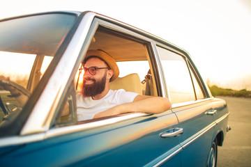 Handsome cool guy driving a vintage car Fototapete
