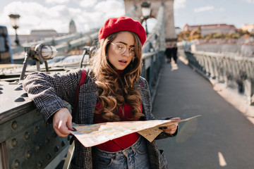 Serious white female traveler looking at map standing on city background. Outdoor photo of woman lost in foreign town during travel.