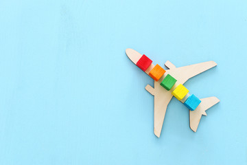 Transportation concept image, man's hand holding toy airplane over blue background