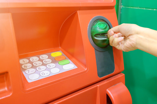 Hand of female insert debit card into automated teller machine (ATM)