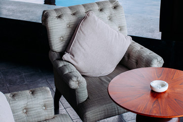 Modern retro grey fabric armchair and pillow with wooden coffee table and ash tray