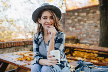 Wall Mural - Ecstatic white woman in casual shirt holding cup of tea on blur autumn background. Outdoor photo of interested european lady in hat with long black nails smiling in october weekend.
