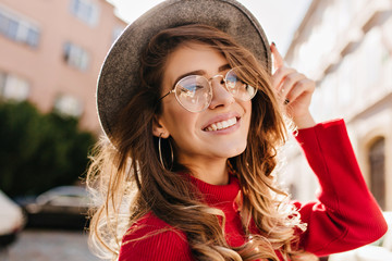 Close-up portrait of cheerful white woman in glasses touching her hat on blur background. Photo of fashionable girl with beautiful brown hair smiling to camera. Wall mural