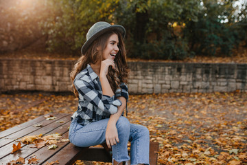 Wall Mural - Romantic white woman with long brown hair looking away with dreamy smile, posing in sunny autumn day. Elegant curly female model with pale skin sitting on bench with green trees behind.
