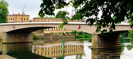 Panorama. Building with reflection in water, bridge over river Moselle. Thionville, France