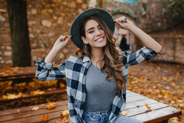 Wall Mural - Fascinating european female model in casual checkered shirt posing with pleasure in yard in autumn. Dreamy white woman in hat enjoying september day.