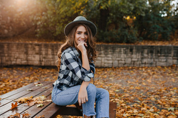 Wall Mural - Spectacular brown-haired girl in casual clothes relaxing in park in good autumn weather. Refined white lady in gray elegant hat posing in sunny morning in yard, covered with fallen leaves.