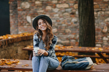 Wall Mural - Lovable european female model wears casual jeans and blue shirt sitting outdoor in warm october weekend. Stunning young woman relaxing in park in autumn day and cute smiling to camera.