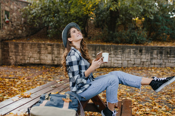 Wall Mural - Refined white woman in stylish casual clothes spending time at countryside in autumn day. Outdoor photo of graceful lady in vintage jeans posing with happy smile in september weekend.