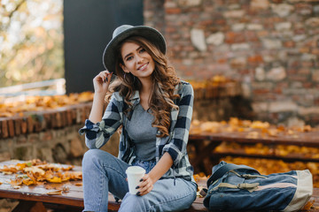 Wall Mural - Interested lady with elegant black manicure drinks coffee on wooden bench with golden leaves on background. Outdoor portrait of gorgeous white female model wears hat and casual shirt chilling in park.
