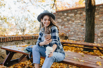 Magnificent white woman wears casual clothes texting message in good september day. Outdoor portrait of pretty girl with sincere smile using phone while chilling in autumn yard.