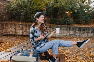 Wall Mural - Carefree girl in vintage jeans fooling around in autumn park, holding phone. Enthusiastic european woman in trendy gray hat waving legs while posing with cup of coffee in yard.