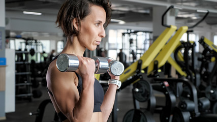 Portrait of athletic mature woman is making set of reps exercise for biceps with dumbbells in hands in gym. She is lifting dumbbells, copy space