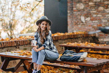Wall Mural - Good-looking girl in short denim pants sitting on wooden table in autumn park. Cute white female model in elegant hat spending time outdoor, drinking coffee in october day.