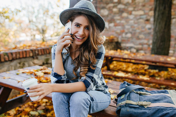 Wall Mural - Stunning blue-eyed lady with curly hairstyle calling friend in good autumn day. Cute european girl in casual jeans talking on phone on autumn background.