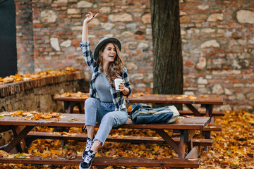 Wall Mural - Emotional female model in short jeans and black shoes drinks coffee in park in warm september morning. Attractive caucasian lady looking away and waving hand in yard covering with yellow leaves.