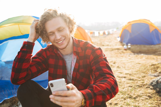 Handsome cheerful man camping