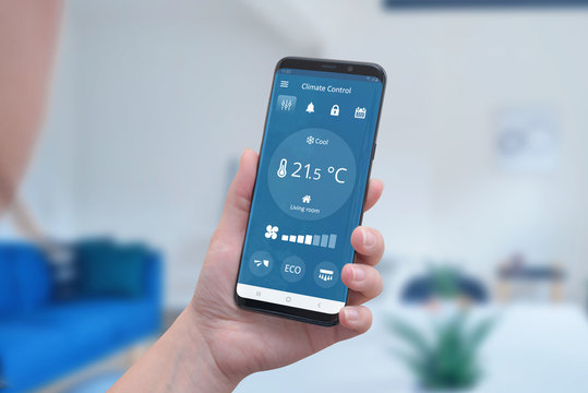 Modern climate control app interface on a smartphone in hand. Concept of simple temperature control and auto heating.