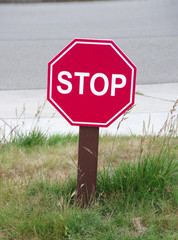 A small STOP sign at an intersection of two driveways in a park