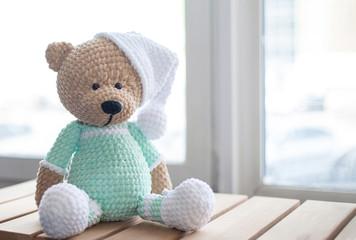 Handmade amigurumi teddy bear on wooden table