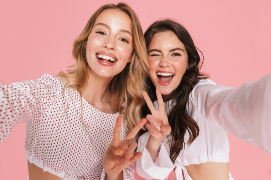 Smiling friends women posing isolated over pink wall background take selfie by camera.