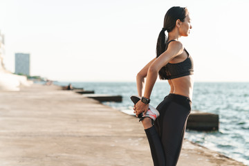 Young strong fitness woman outdoors at the beach at morning make stretching exercises.
