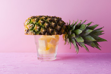 Pineapple and infused water on a pink background. Half of pineapple on a pastel background....