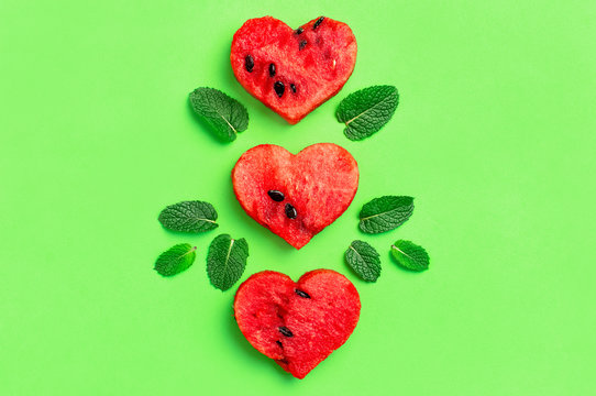 Creative summer food concept. Juicy slices of ripe red watermelon in the shape of a heart and mint leaves on green background. Flat lay, top view, copy space. Watermelon pattern. Love for watermelon