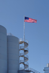 The US flag in the wind on the top of a circular staircase at modern industrial silos under blue sky