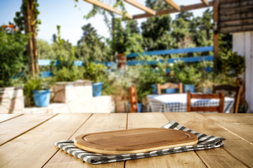 Wooden cutting board  background with a garden view in distance