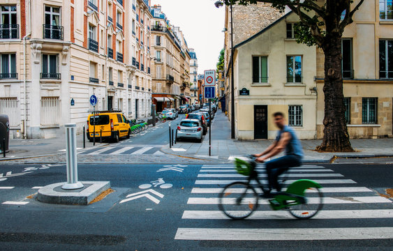 Unidentifiable man cycling down the street. The public bike system in Paris