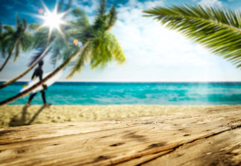 Wooden table background in the beautiful ocean and sunny sky view with palm leaves