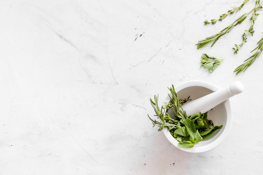 Homeopathy with leaves and healing herbs for making oil on white marble background top view copyspace