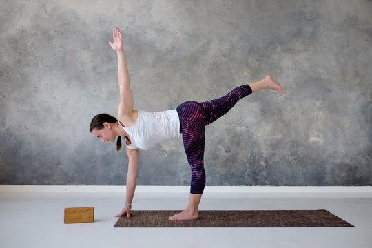 Young yogi attractive woman practicing yoga standing in twisted Half Moon exercise, Ardha Chandrasana pose. Studio shot