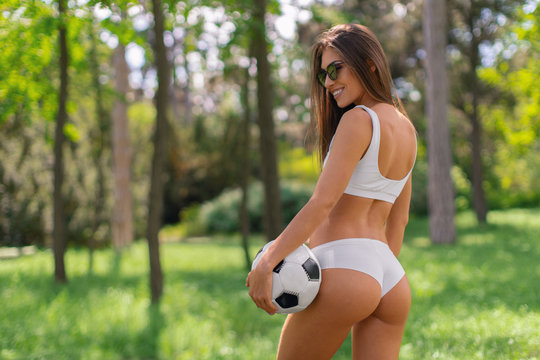 Young sexy girl in white sportswear with a soccer ball