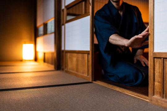 Traditional japanese house or ryokan with man in kimono opening shoji sliding doors sitting on tatami mat floor