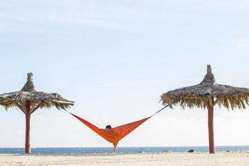 Woman sitting in a hammock on the beach between two palapas