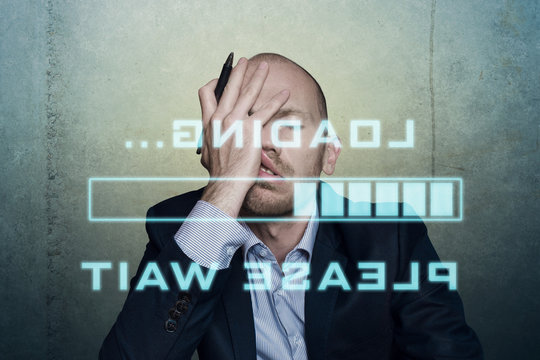 businessman or office worker waits bored and long on his slow computer or internet connection, displaying a loading bar and a message