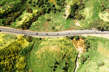 Aerial view of cars driving on road through green landscape